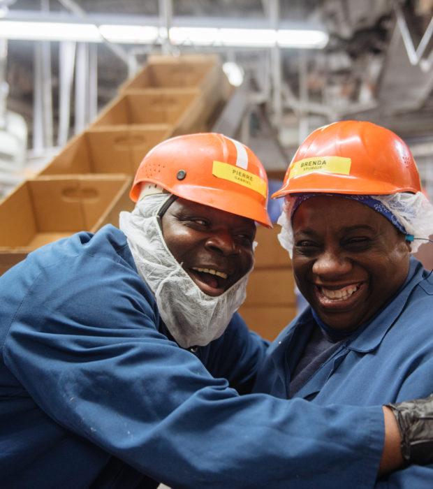 two men smiling in work gear