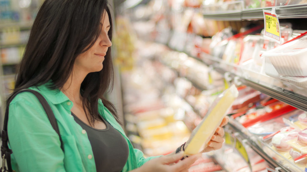 Woman wearing a green shirt is checking a tray of frozen meat in a supermarket