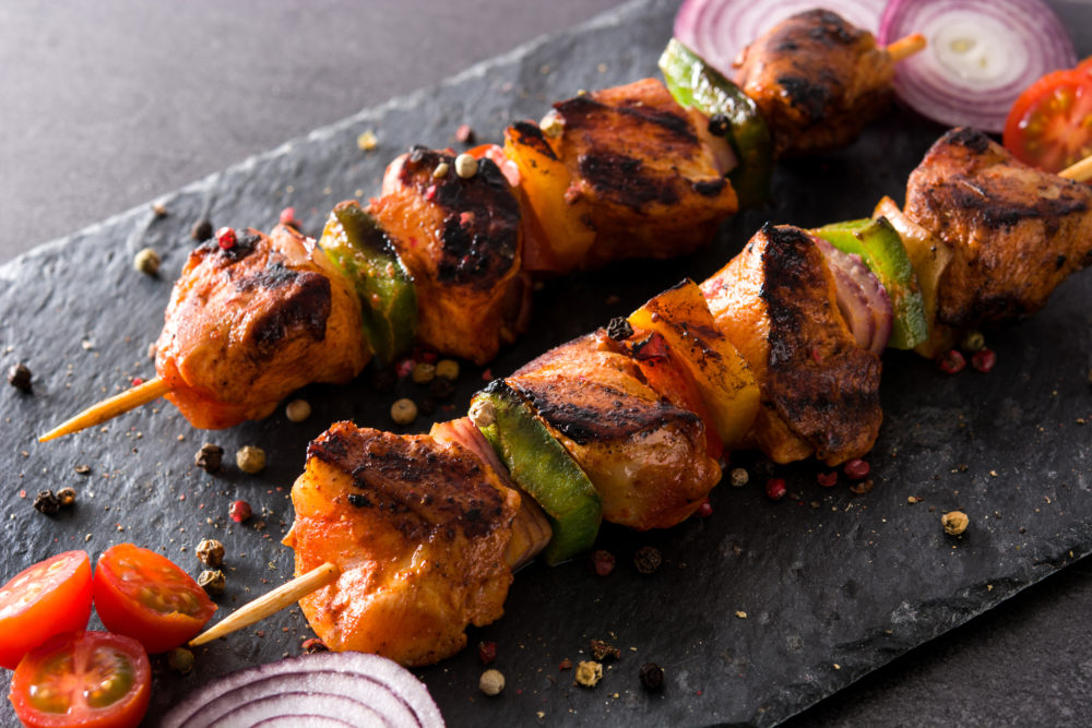 Chicken shish kebab with vegetables on black stone