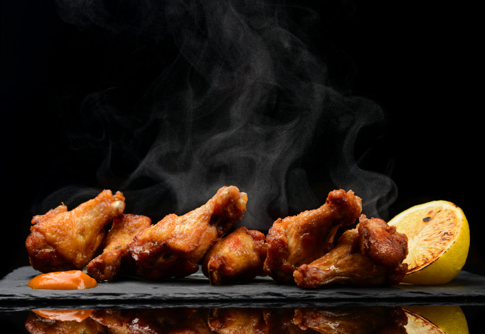 Hot and spicy bbq chicken wings with dip and hot sauce on black stone plate